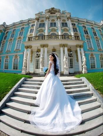 Im Brautkleid vor einem Schloss
